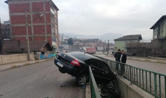 Yoldan çıkan otomobil su kanalında askıda kaldı