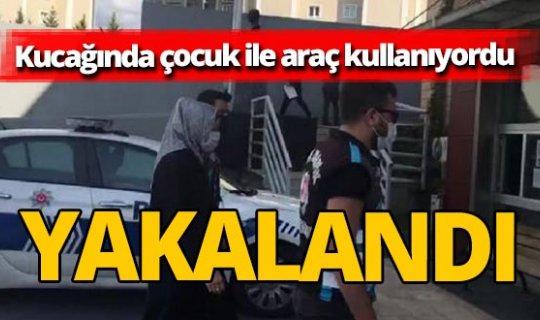 Kucağında çocuk ile  otomobil kullanırken polislere yakalandı