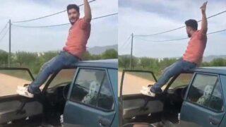 Aracın tavanına oturup ayaklarını kapıya dayadı